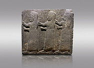 Picture & image of Hittite monumental relief sculpted orthostat stone panel of a Procession Basalt, Kargamis, Gaziantepe, 900 - 700 B.C. Anatolian Civilisations Museum, Ankara, Turkey.<br /> <br /> It is a depiction of three marching female figures in long dress with a high headdress at their head. These women are considered to be the nuns of the Goddess Kubaba. The figures in the front and behind have a bunch of spicy in their right hand while the figure in the middle has an empty right hand. Figures carry objects similar to a sceptre in their left hand. <br /> <br /> Against a gray background. .<br />  <br /> If you prefer to buy from our ALAMY STOCK LIBRARY page at https://www.alamy.com/portfolio/paul-williams-funkystock/hittite-art-antiquities.html  - Type  Karkamıs in LOWER SEARCH WITHIN GALLERY box. Refine search by adding background colour, place, museum etc.<br /> <br /> Visit our HITTITE PHOTO COLLECTIONS for more photos to download or buy as wall art prints https://funkystock.photoshelter.com/gallery-collection/The-Hittites-Art-Artefacts-Antiquities-Historic-Sites-Pictures-Images-of/C0000NUBSMhSc3Oo