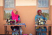 View of two women sitting in front of Design and Tailoring Centre with sewing machines, Musoto, Uganda
