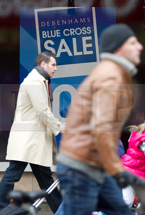 © Licensed to London News Pictures. 08/01/2013. London, UK.  Shoppers walk past signs for the Debenham's 'Blue Cross Sale' displayed in the chain's flagship Oxford Street store in London today (08/01/13).  The department store chain today reported record December sales, achieved in part by additional promotions, with like-for-like sales rising by 2.9% compared to the same period in 2011/12 and online sales boosted by 39%.  Photo credit: Matt Cetti-Roberts/LNP