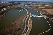 Nederland, Limburg, gemeente Maastricht, 07-03-2010; waterhuishouding van de Maas, de stuw Borgharen (r) met vistrap. Het eiland Bosscherveld is gedeeltelijk afgegraven, de Maas kan bij hoogwater in de toekomst ook over het eiland stromen. Het water geheel links leidt naar een overlaat. In het midden aan de horizon het dorp Borgharen. De Maas vormt de grens met Belgie (links van de rivier)..Water management of the Meuse, Borgharen weir (r) with fish ladder. The island Bosscherveld has been partially excavated,  in the future the Meuse will stream over the island.The river Meuse is called the Border Meuse - forms the border with Belgium (l)..luchtfoto (toeslag), aerial photo (additional fee required).foto/photo Siebe Swart