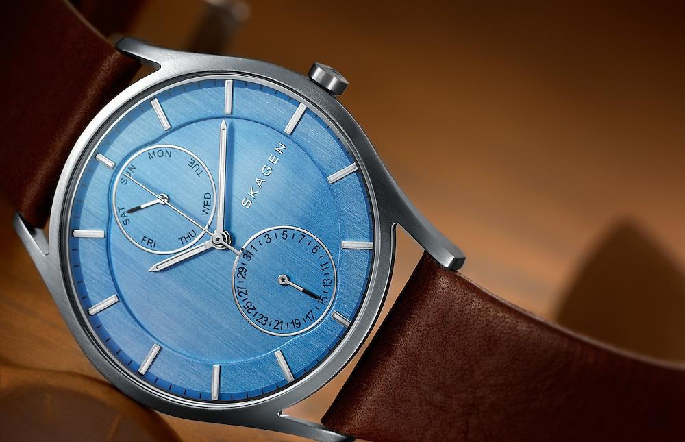 Skagen watch with blue face lying on it's side on a sheet of copper.
