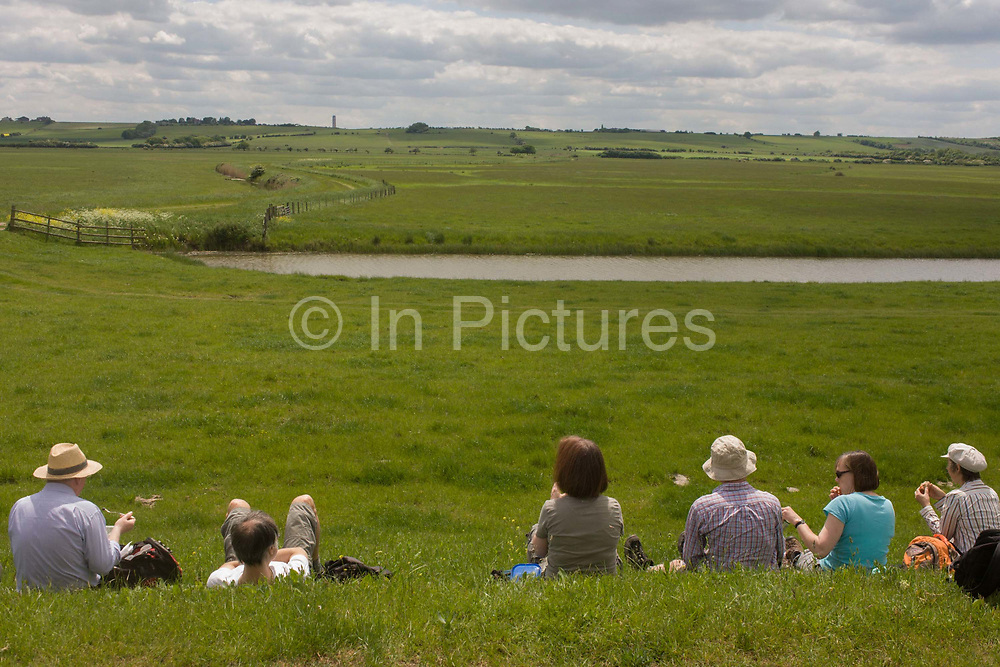 A group of country ramblers rest for lunch on the sea defence embankment of Halstow Marshes on the Kent Thames estuary marshes, potentially threatened by the future London airport. With the panoramic views beyond, the walkers have stopped at mid-day in sheltered sunshine to admire the landscape that could controversially become the site for London's estuary airport, built on reclaimed and marshland on the river Thames, east of the city. Current London mayor Boris Johnson is in faviour of this project to alleviate pressure from other airport hubs, regardless of wildlife (especially a nearby protected bird sanctuary).