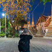 Man takes photos of buddist temple Phra Maha Chedi at night, Bangkok, Thailand