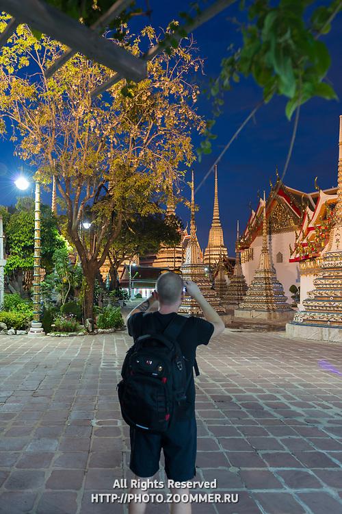 Man takes photos of buddist temple Phra Maha Chedi at night, Bangkok, Thailand