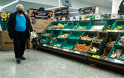 © Licensed to London News Pictures. 17/10/2021. London, UK. A shopper walks past nearly empty shelves of fruit and vegetables in Morrisons, north London, amid fears of Christmas food shortages due to labour shortages, following Brexit. It has been reported that number of ships from Asia are forced to turn away at Felixstowe, the UK's biggest container port because of a backlog of containers caused by the HGV driver shortage. Photo credit: Dinendra Haria/LNP