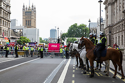 London, UK. 9th June, 2018. Mounted police officers maintain a sterile area in Parliament Street in front of anti-fascists protesting against the far-right March for Tommy Robinson.