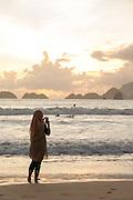 Woman taking photograph of surfers, Red Island Beach, Red Island, Banyuwangi Regency, East Java, Indonesia, Southeast Asia