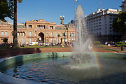 Fountain with rainbow effect outside the Casa Rosada, Placa de Mayo, Buenos Aires, Federal District, Argentina.