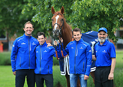 Trainer Charlie Appleby (left), day to day jockey Brett Doyle (centre left), winning jockey William Buick (centre right) and groom Saeed pose with Masar during the homecoming event at Moulton Paddocks, Newmarket.