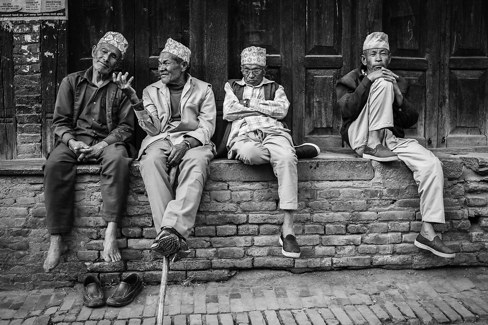 A group of friends sitting together on the street of Bakthapur, Nepal. Photo by Lorenz Berna