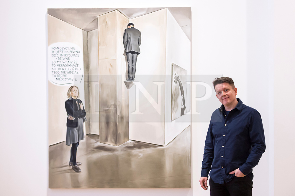 """© Licensed to London News Pictures. 28/11/2019. LONDON, UK. Polish artist Marcin Maciejowski poses with his work """"It Certainly Has A Fairly Intriguing - Strange Composition"""", 2019.  First look of """"Private View"""" by Marcin Maciejowski at Galerie Thaddeus Ropac in Mayfair.  The artist's first London exhibition features new large-scale paintings and graphic works on paper merging comic-book and Old Master traditions.  The show runs 28 November to 25 January 2020. Photo credit: Stephen Chung/LNP"""