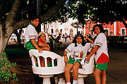 Female group of pilgrims to the Basilica de Guadelupe seating in Parque Francisco Canton Rosado wearing Our Lady of Guadelupe shirts.