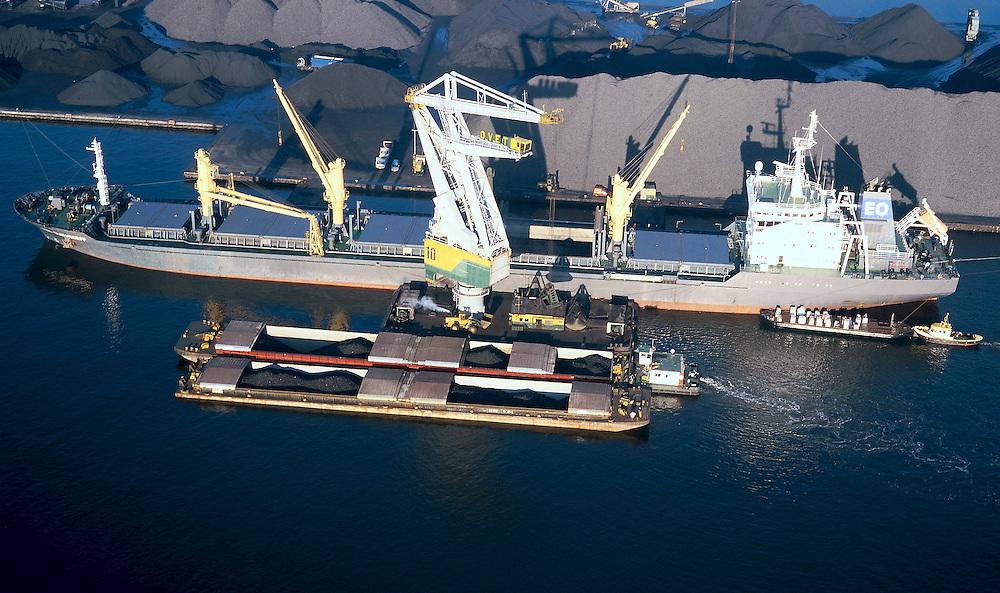 Nederland, Zeeuwsch-Vlaanderen, Terneuzen, 15-11-2001; overslag van kolen naar lichters (duwbakken) in de haven van Terneuzen, gelegen aan Kanaal Terneuzen-Gent (zie ook overzichtsfoto); parlevinker aan stuurboordzijde bij brug; van zeeschip naar binnenvaart schip; transshipment of coal to barges in the port of Terneuzen, located at Ghent-Terneuzen canal (also overview);kustvaart, scheepvaart, havenkraan, steenkool, erts, coastal shipping, coaster, port, crane, coal, ore.<br /> luchtfoto (toeslag), aerial photo (additional fee)<br /> photo/foto Siebe Swart