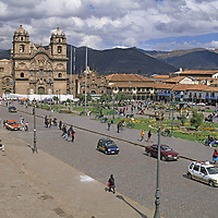 Churches, cathedrals and businesses surround a central square in Cuzco, Peru.