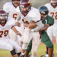 Tohatchi Cougar Rayshawn Whitney (14) is pulled down Wingate Bear Ty Martinn (54)  Friday at Wingate High School.