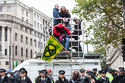 London, UK. 7 October, 2019. Metropolitan Police officers surround climate activists from Extinction Rebellion who glued themselves to a scaffold tower to block Trafalgar Square on the first day of International Rebellion protests to demand a government declaration of a climate and ecological emergency, a commitment to halting biodiversity loss and net zero carbon emissions by 2025 and for the government to create and be led by the decisions of a Citizens' Assembly on climate and ecological justice.