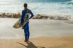 A surfer standing on Fistral beach in Newquay, Cornwall.