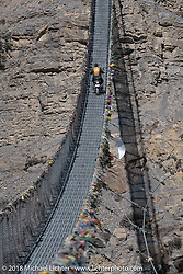 Kelly Modlin riding across a narrow suspension bridge over the Kali Gandaki River on day-6 of our Himalayan Heroes adventure riding from Muktinath to Tatopani, Nepal. Sunday, November 11, 2018. Photography ©2018 Michael Lichter.