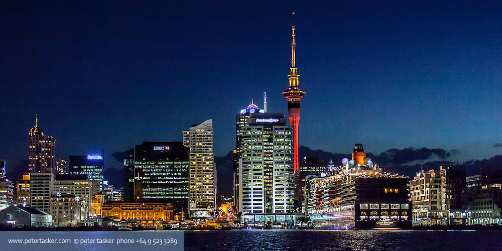 Cruise liner, Queen Elizabeth, along side the Hilton Hotel, Auckland, New Zealand. Photographed at night, with downtown Auckland in background.