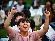 "15 JUNE 2018 - SEOUL, SOUTH KOREA: A South Korean teenager cheers during a rally to mark the anniversary of the signing of the June 15th North–South Joint Declaration between South Korea and North Korea. The Declaration was negotiated by late South Korean President Kim Dae-jung and North Korean leader Kim Jong-il and signed on 15 June 2000. It was a part of South Korea's ""Sunshine Policy,"" which guides the South's relationship with North Korea. This year's observance of the anniversary was bolstered by the recent thawing in relations between North Korea and South Korea and the US.   PHOTO BY JACK KURTZ"