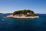 The island of Gale?nik, in the Paklinski archipelago, near Hvar, Croatia, with a boat passing by