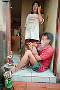 """Mar. 19, 2009 -- BANGKOK, THAILAND: A man smokes a water pipe in the doorway of his home in the Ban Krua section of Bangkok. The Ban Krua neighborhood of Bangkok is the oldest Muslim community in Bangkok. Ban Krua was originally settled by Cham Muslims from Cambodia and Vietnam who fought on the side of the Thai King Rama I. They were given a royal grant of land east of what was then the Thai capitol at the end of the 18th century in return for their military service. The Cham Muslims were originally weavers and what is known as """"Thai Silk"""" was developed by the people in Ban Krua. Several families in the neighborhood still weave in their homes.   Photo by Jack Kurtz"""