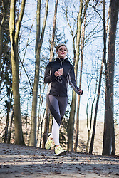 Fit woman with smart phone and headphones jogging on forest path