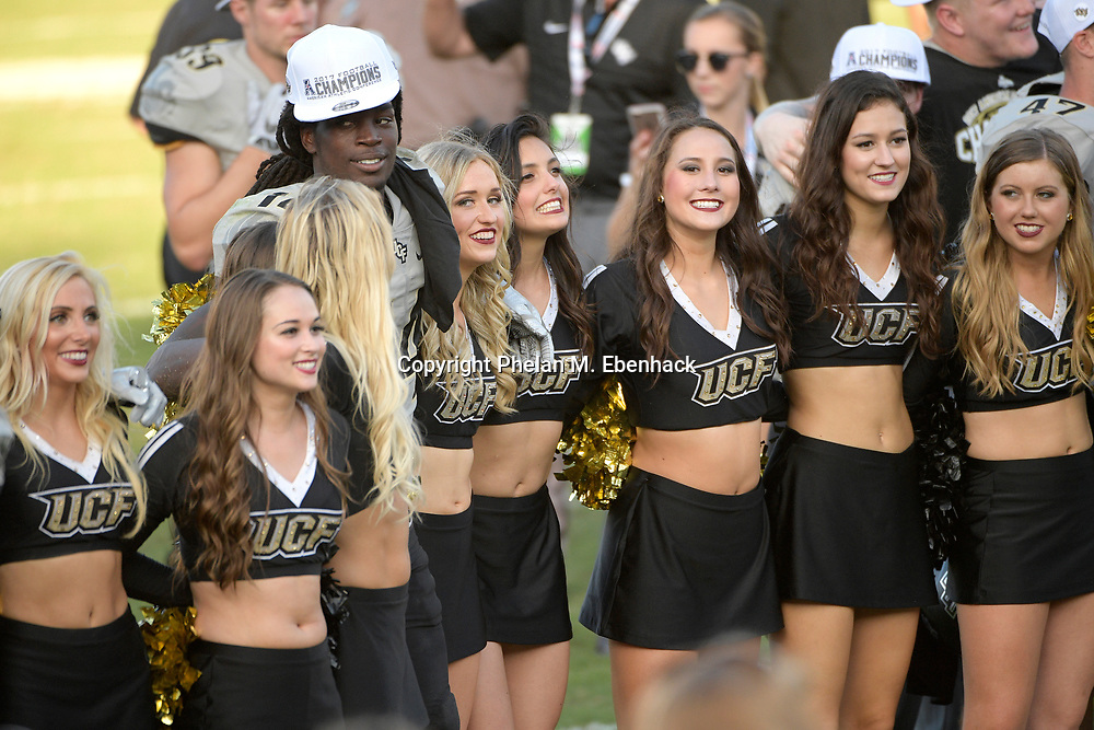 Central Florida defensive back Nevelle Clarke (14) stands with cheerleaders during a singing of the school song after the American Athletic Conference championship NCAA college football game against Memphis Saturday, Dec. 2, 2017, in Orlando, Fla. Central Florida won 62-55. (Photo by Phelan M. Ebenhack)