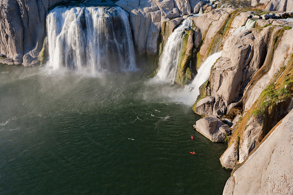 Kayakers below the spillway of Shoshone Falls give a sense of scale to the water drop of 212 feet.  Licensing and Open Edition Prints.