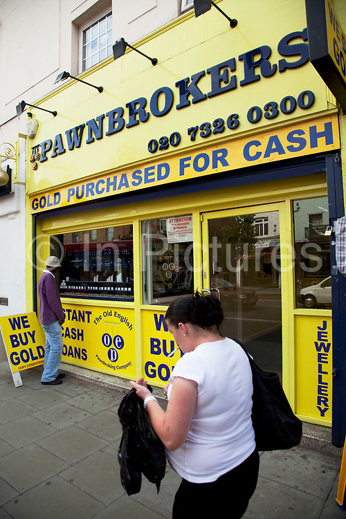 Pawnbrokers shop on Camberwell Road in South London. This is a a multicultural area in South London where different people of all nationalities and races mix together. A pawnbroker is an individual or business (pawnshop or pawn shop) that offers secured loans to people, with items of personal property used as collateral. The word pawn is derived from the Latin pignus, for pledge, and the items having been pawned to the broker are themselves called pledges or pawns, or simply the collateral.<br /> If an item is pawned for a loan, within a certain contractual period of time the pawner may purchase it back for the amount of the loan plus some agreed-upon amount for interest.
