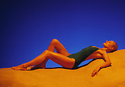 Beautiful slim woman reclining on sand dune beach set with golden light on her and rich blue background. She is wearing a one piece green bathing suit.