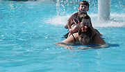 A mother and two children boy aged 5 and girl aged three playing in a swimming pool. Model Release available