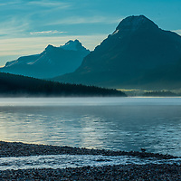 Morning mist rises over Bow Lake in Banff National Park, Alberta, Canada. Behind are (L to R) Mount Andromache, Mount Hector and Bow Peak.