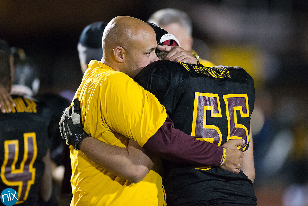 JM Robinson Bulldogs head coach Joe Glass hugs Ethan Steinbacher (55) following their 1-point loss to the South Iredell Vikings in the second round of the NCHSAA 3A playoffs at South Iredell High School November 20, 2015, in Statesville, North Carolina.  The Vikings defeated the Bulldogs 14-13.  (Brian Westerholt/Special to the Tribune)