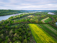 Lush spring greens follow the Ohio River as it snakes between Ohio and West Virginia carrying a steady flow of river boats in its waters.