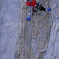 BAFFIN ISLAND, Nunavut, Canada, Mark Synnott (MR) free climbs on first pitch of upper wall, Great Sail Peak, an Arctic big wall rock climb.