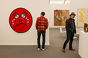 New York, NY - May 3, 2019. A man contempltes a fabric piece with a sad face by Amanda Ross-Ho in the Mitchell-Innes & Ross Gallery at the Frieze Art Fair on New York City's Randalls Island.