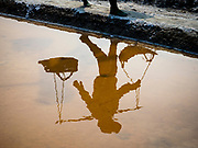 28 MARCH 2018 - BAN LAEM, PHETCHABURI, THAILAND: The shadow of a worker walking out to a salt field during the 2018 salt harvest in Petchaburi province, about two hours south of Bangkok. Sea salt is made in provinces south of Bangkok by flooding fields with ocean water after the rainy season. As the fields dry out from evaporation, workers go into the fields and gather the salt left behind.      PHOTO BY JACK KURTZ