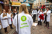 Oxfam supporters meet outside Hammersmith tube station preparing for an action outside Coca Cola headquarters, calling for the company to tighten its supply chain so that the ingredients Coca Cola uses in its products are not grown on land that has been grabbed from poor communities