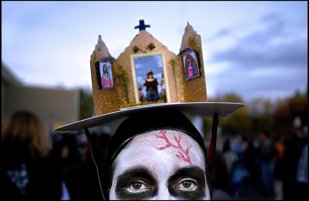 .Marla Martinez wears a Dia de los Muertos altar during an evening celebration at the Westside Community Center following the parade in Albuquerque's South Valley on Sunday.