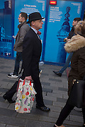 A rare, traditionally-dressed businessman wearing a bowler hat and bow tie walks past carrying shopping, on 9th December 2016, in the City of London.