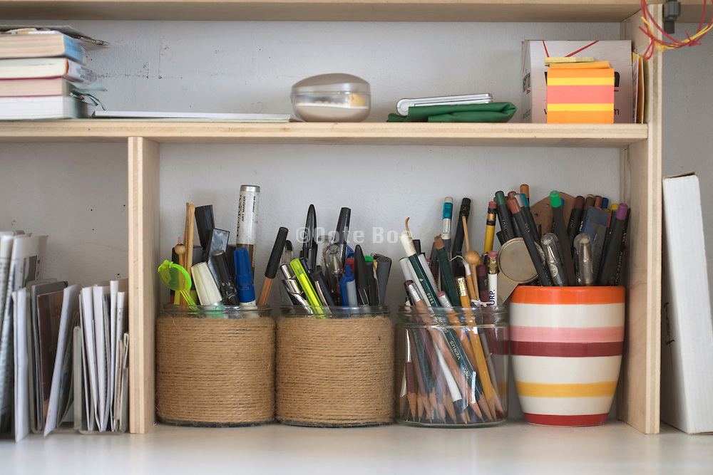 row with pens and pencil neatly stacked in pots