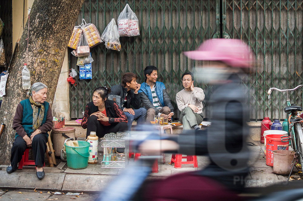 Motorbike passing by a street vendor in the old quarter of Hanoi, Vietnam, Southeast Asia