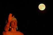 The full moon of July rises behind the statue of an American Indian at the Orange County Fairgrounds in Mechanicstown, N.Y..July 21, 2005.