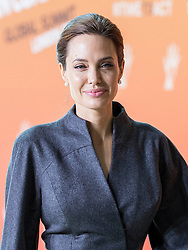 Angelina Jolie arrives alongside Brad Pitt at the End Sexual Violence in Conflict Summit at the Excel Centre. Image ©Licensed to i-Images Picture Agency. 13/06/2014. London, United Kingdom. Angelina Jolie and Brad Pitt. the Excel Centre. Picture by i-Images