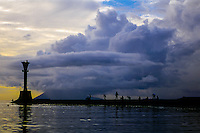 Indonesia, Sulawesi, Manado. Manado harbour with a lighthouse on the pier. Manado Tua, an extinct volcano, in the background.