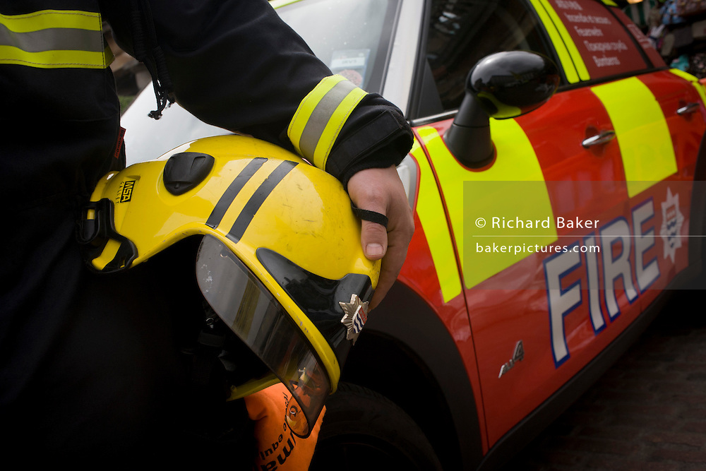 Detail of a firefighter's helmet and a London Fire Brigade's Mini car after the LFB's 'extrication' team with the Vehicle and Operator Services Agency (VOSA) gave a demonstration on how firefighters rescue passengers by cutting open with dedicated cutting equipment a stretch limousine in London's Covent Garden Piazza. Highlighting the dangers of hiring illegal luxury or novelty cars, this vehicle was seized last year with many mechanical defects rendering it unsafe for those inside with limited exit doors. Of 358 cars stopped in March 2012, 27 were seized and 232 given prohibitions. This scenario is a simulation and therefore reproduces the reality of an emergency, using real emergency services personnel and equipment. Casualties are volunteers and none were injured in the making of this photograph.