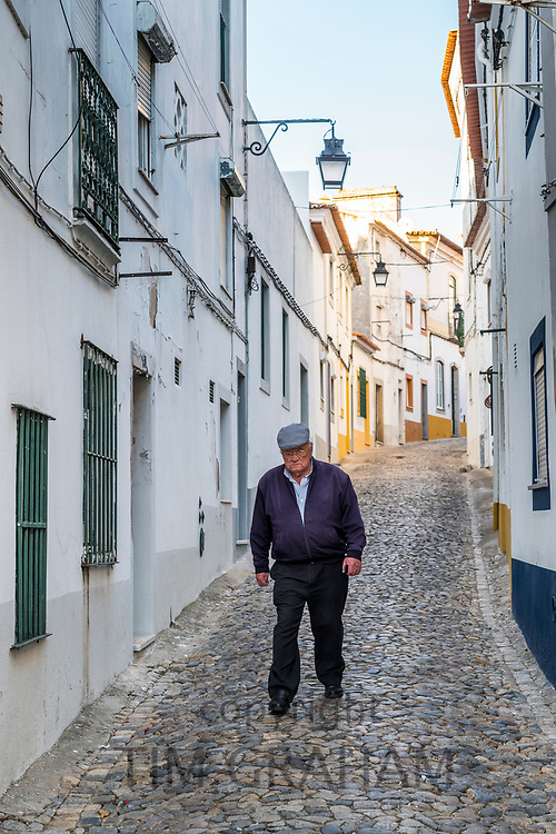 Elderly man in flat cap walking in typical street scene of white and yellow houses, lanterns and narrow cobble street in Evora, Portugal