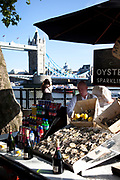 Scene of the River Thames, London. Running through the heart of the city. Man selling Oysters and Champagne near to Tower Bridge