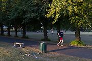 An early runner passes a waste bin the morning after a late-night party by park-users during the Coronavirus pandemic in Ruskin Park, on 30th July 2020, in Lambeth, south London, England.